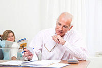 Man doing paperwork with woman sitting in background