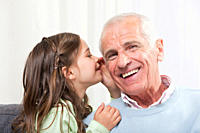 Girl 6_7 whispering into grandfather's ear, close_up