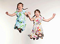 Girls 6-7 holding hands and jumping, smiling (thumbnail)