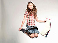 Girl 8_9 holding book and jumping, smiling, portrait
