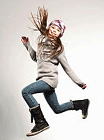 Girl 8_9 wearing woolly hat jumping, smiling, portrait