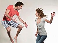 Man and woman shouting and jumping against gray background