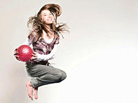 Girl 12_13 holding ball and jumping, portrait