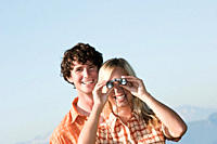 Young couple standing, woman uses binoculars