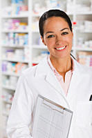 Smiling pharmacist in drug store holding clipboard