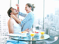 Playful woman feeding strawberry to husband at breakfast