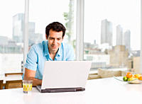 Man using laptop with cityscape in background