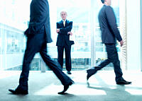 Businessman standing in corridor as co_workers rush past