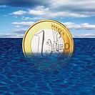 One euro coin drowning in sea, close_up
