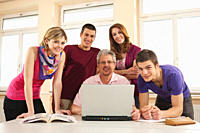 Germany, Emmering, Teacher and students using laptop, smiling, portrait