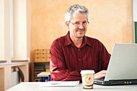 Germany, Emmering, Senior man using laptop, portrait, smiling