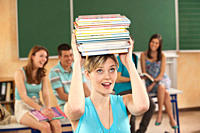 Germany, Emmering, Young woman carrying stack of books with students in background
