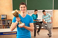 Germany, Emmering, Young man holding trophy with students in background