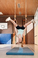 Germany, Emmering, Girl 12_13 hanging from flying rings, smiling, portrait