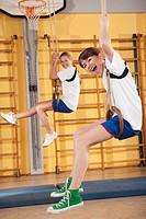 Germany, Emmering, Girls 12_13 hanging from gymnastic rings, smiling, portrait