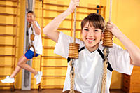 Germany, Emmering, Girls hanging from gymnastic rings, smiling, portrait