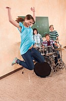 Germany, Emmering, Girl jumping with boys in background playing drums