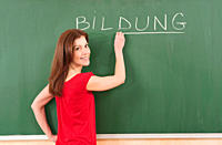 Germany, Emmering, Woman writing text bildung on blackboard, smiling, portrait
