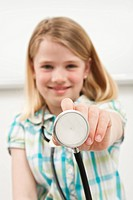 Germany, Munich, Girl 8_9 holding stethoscope, smiling, portrait