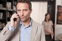 Germany, Man on the phone with woman standing in background