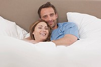 Germany, Couple lying on bed, portrait, smiling