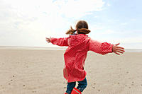Germany, North Sea, St.Peter_Ording, Girl 6_7 in rain coat playing on beach, rear view