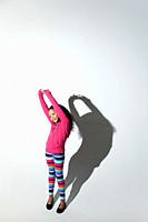 Girl with arms raised and shadow