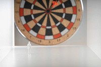 Businessman figurine standing in front of dartboard.