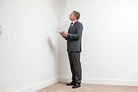 Mature man examining damp patch on wall