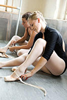 Ballerinas putting on ballet slippers