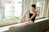 Ballerina sitting on windowsill