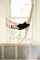 Ballerina stretching in window