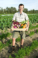 Man holding wooden create of freshly farmed vegetables (thumbnail)