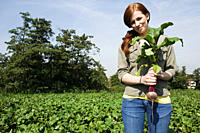 Young woman holding fresh beetroot in field