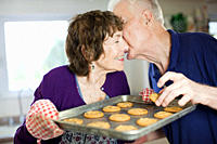 Senior couple kissing with home baked cookies (thumbnail)