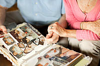 Senior couple with at family album (thumbnail)