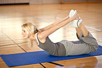 Germany, Mauern, Woman lying and stretching on exercise mat, smiling
