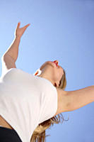 Woman stretching out arms in front of blue sky, low angle view