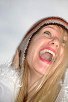 Young woman wearing knitted cap, running and laughing at the beach, close up