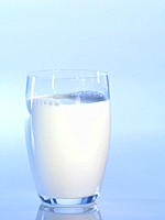 Glass of milk against blue background, close_up