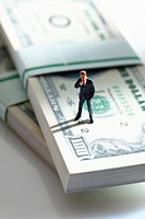 Manager figurine standing on bundle of 100 us dollar notes