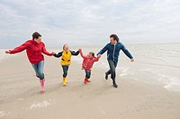 Germany, St. Peter_Ording, North Sea, Family holding hands and running on beach