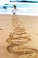 Young child at the beach creating swirling footmarks in the sand