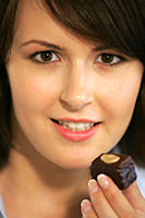 Young woman eating chocolate candy, portrait, close up