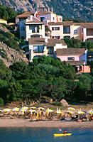 Kayaking on beach with vacation homes, Porto Cervo, Sardinia, Italy