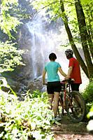 Austria, Salzkammergut, Mondsee, Young Couple watching waterfall