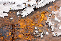 Ice and frost patterns along edge of small creek in early winter