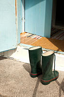 Two wellington boots in front of an open door