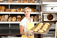 A woman pulling a tray of freshly baked rolls in a bakery