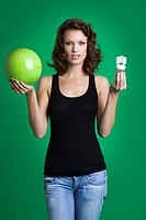 Young woman holding green ball and light bulb (thumbnail)